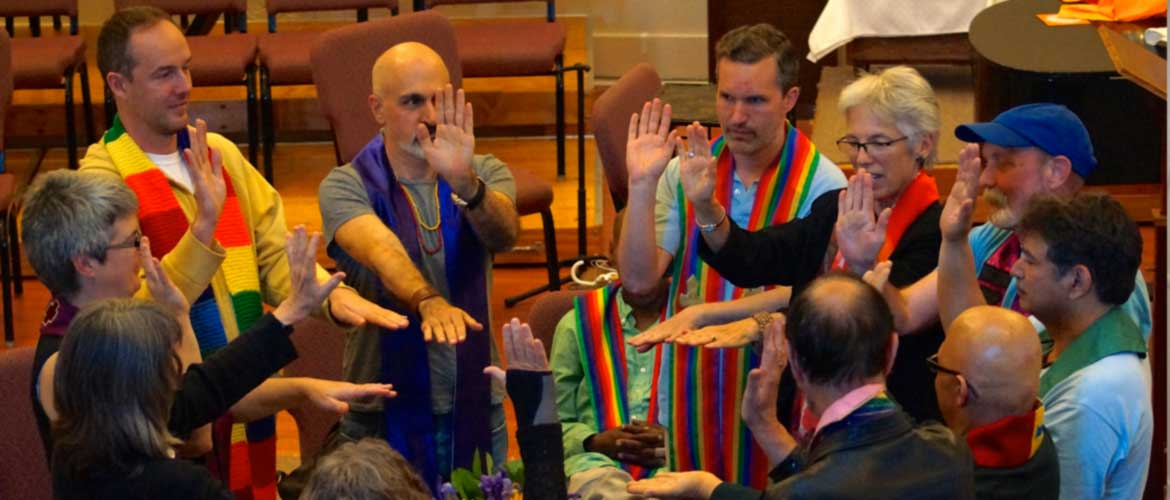 Queer Eucharist folks all wearing stoles and gathered in a circle with arms reaching towards the center